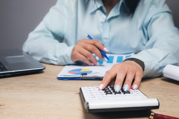 Geschäftsfrau, die mit einem taschenrechner rechnet und daten im büro studiert