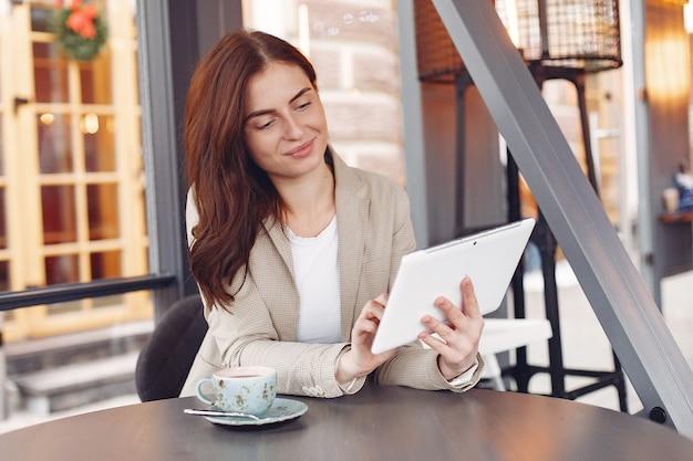 Geschäftsfrau, die mit einer tablette am tisch sitzt