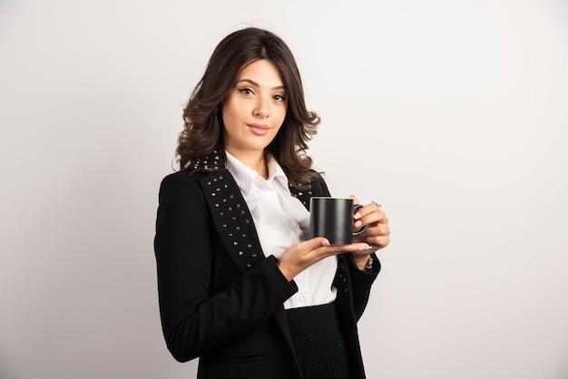 Geschäftsfrau, die mit einer tasse tee auf weiß steht
