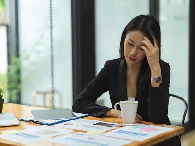 Geschäftsfrau, die mit geschäftsberichten über den geschäftsplan für das nächste jahr nachdenkt und betont