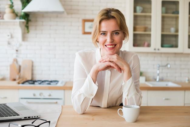 Geschäftsfrau, die mit kaffeetasse und laptop sitzt