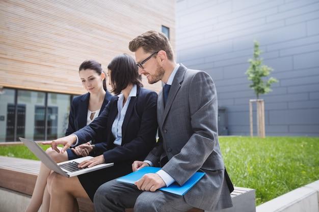 Geschäftsfrau, die mit kollegen sitzt und laptop verwendet