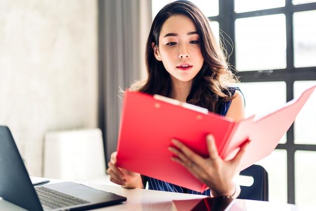 Geschäftsfrau, die mit laptop-computer sitzt und arbeitet kreative geschäftsleute, die in ihrem arbeitsplatz am modernen arbeitsdachboden planen