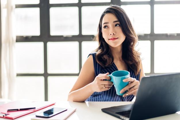 Geschäftsfrau, die mit laptop-computer sitzt und arbeitet und kaffee trinkt. kreative geschäftsleute, die in ihrer arbeitsstation am modernen arbeitsloft planen