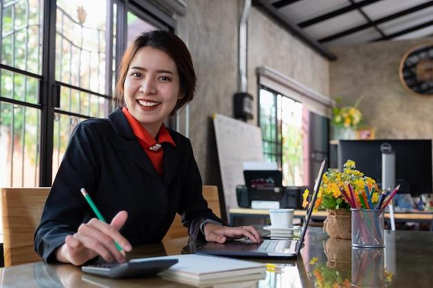 Geschäftsfrau, die mit laptop im arbeitsplatz arbeitet. büroangestellter und porträtkonzept