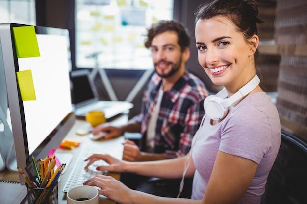 Geschäftsfrau, die mit männlichem kollegen am computertisch arbeitet