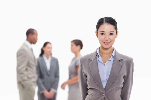 Geschäftsfrau, die mit mitarbeitern im hintergrund lächelt