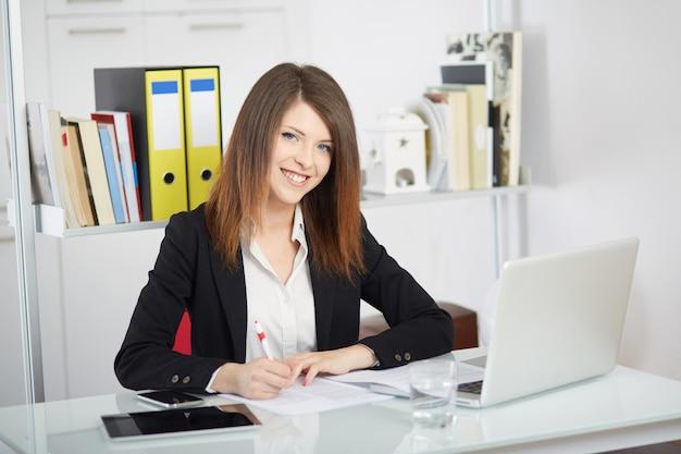 Geschäftsfrau, die mit mobile spricht und im büro mit laptop arbeitet