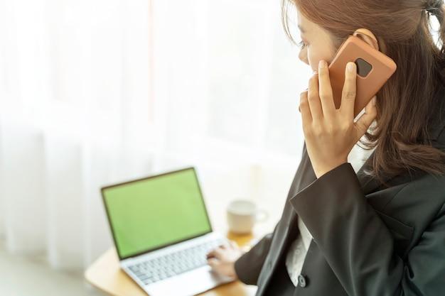 Geschäftsfrau, die mit mobile und laptop im büro arbeitet
