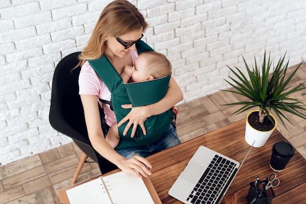 Geschäftsfrau, die mit neugeborenem im tragetuch arbeitet