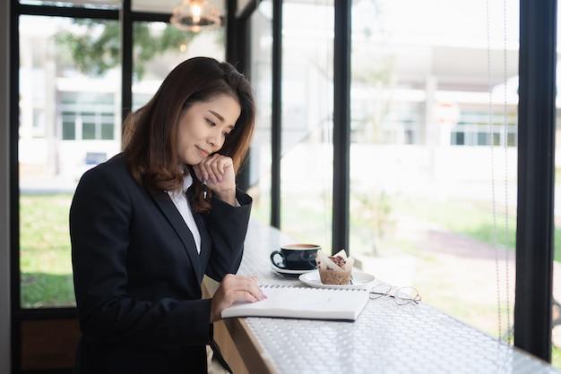 Geschäftsfrau, die mit notizbuch auf dem tisch, geschäftskonzept arbeitet