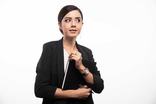 Geschäftsfrau, die mit notizbuch auf weißer wand aufwirft.