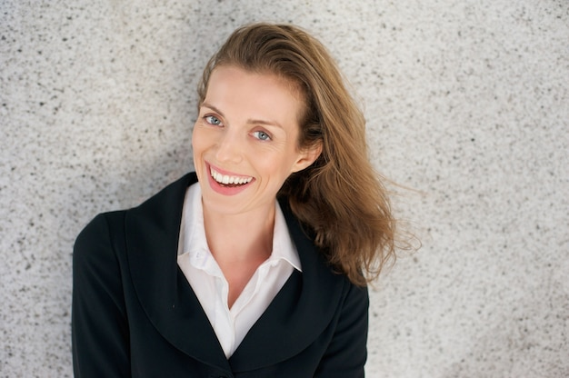 Geschäftsfrau, die mit schwarzer jacke und weißem hemd lacht