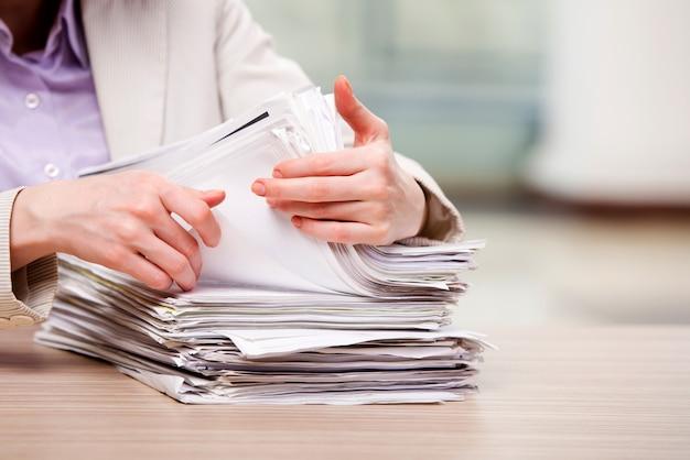 Geschäftsfrau, die mit stapel papieren arbeitet