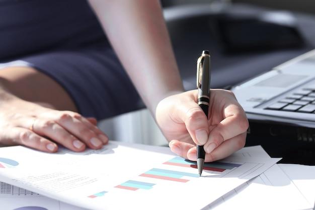 Geschäftsfrau, die mit stift in der büroarbeitsplatzgeschäftsfrau schreibt