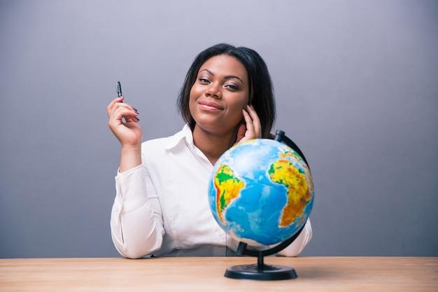 Geschäftsfrau, die mit stift und globus am tisch sitzt