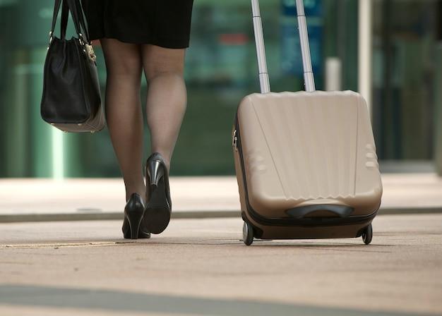 Geschäftsfrau, die mit tasche und koffer geht