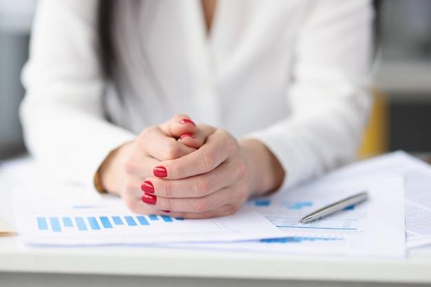 Geschäftsfrau, die mit vielen papierdokumenten am tisch sitzt