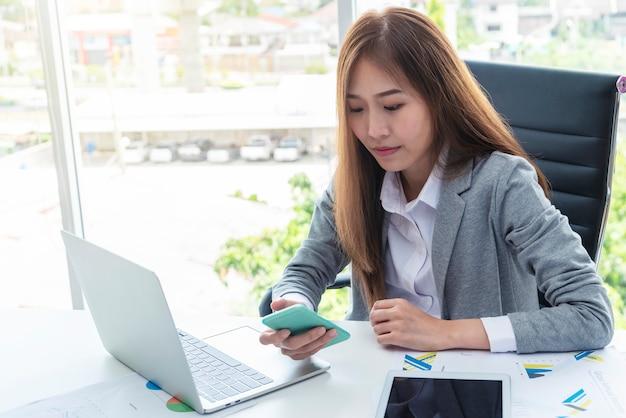 Geschäftsfrau, die mobile mit laptop auf schreibtisch im büro verwendet.