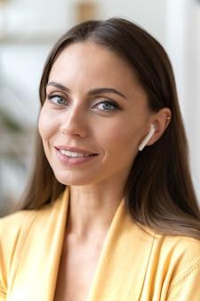Geschäftsfrau, die modernes kopfhörer-gadget verwendet, um mit kunden oder kunden mit mobilen kopfhörern zu sprechen