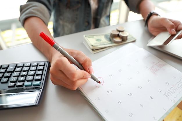 Geschäftsfrau, die monatlich zahlt und kreditkarten hält und auf kalender schreibt