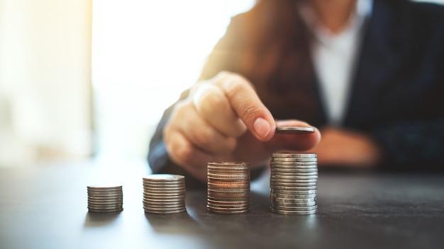 Geschäftsfrau, die münzen auf dem tisch hält und stapelt