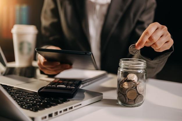 Geschäftsfrau, die münzen hält, die in glas mit smartphone und taschenrechner setzen, um konzept zu berechnen, das geld für finanzbuchhaltung spart