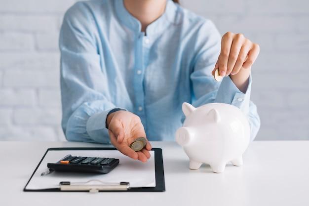Geschäftsfrau, die münzen mit weißem piggybank auf schreibtisch zeigt
