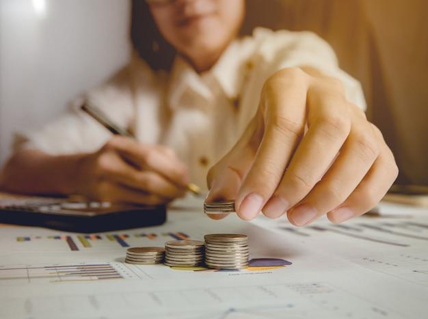Geschäftsfrau, die münzen und das stapeln auswählt. es gibt die rechte hand, die einen stift im hintergrund hält. geringe schärfentiefe. fokus an der fingerspitze.
