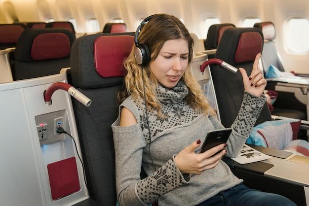 Geschäftsfrau, die musik hört und sich während des fluges mit dem flugzeug in der ersten klasse entspannt