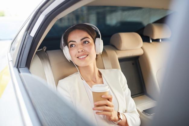 Geschäftsfrau, die musik im taxi hört