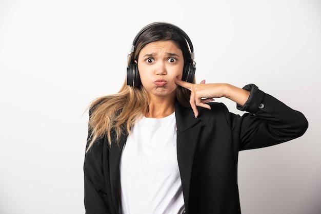 Geschäftsfrau, die musik in kopfhörern hört.