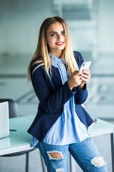 Geschäftsfrau, die nachricht mit smartphone im büro sendet