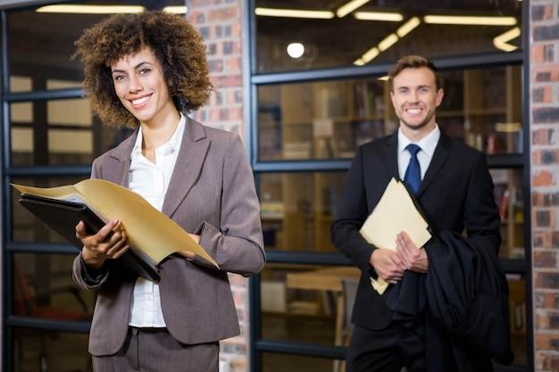 Geschäftsfrau, die nahe bibliothek steht und dokumente betrachtet