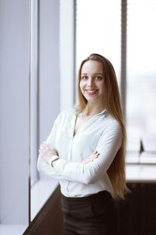 Geschäftsfrau, die nahe dem fenster im korridor des büros steht.