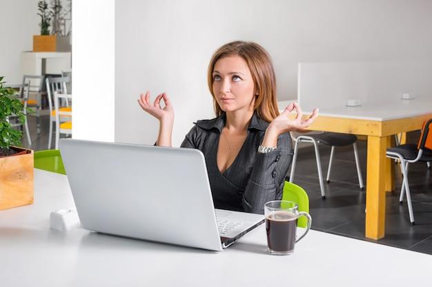 Geschäftsfrau, die nahe laptop meditiert. entspannter büroangestellter, der während einer kaffeepause yoga-meditation macht