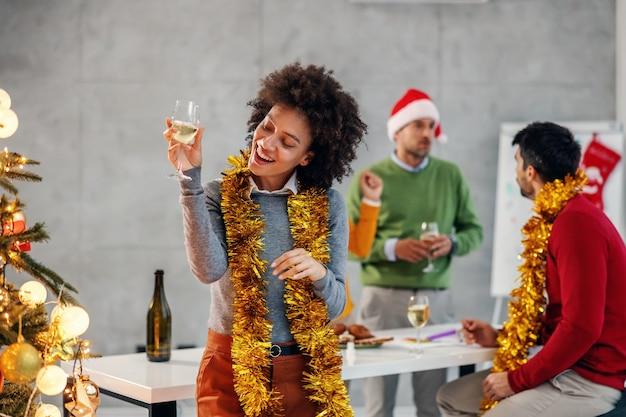 Geschäftsfrau, die neben weihnachtsbaum steht und große zeit am heiligabend in ihrer firma hat.