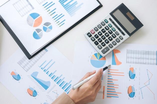 Geschäftsfrau, die neue planfinanzdiagrammdaten über laptop bearbeitet und finanzen tut