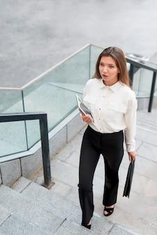 Geschäftsfrau, die oben die treppe klettert