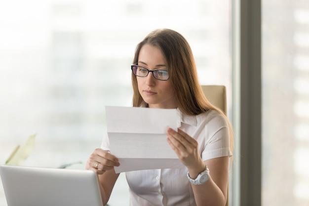 Geschäftsfrau, die offizielles dokument am arbeitsplatz liest