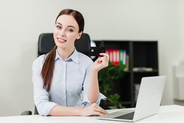 Geschäftsfrau, die online-zahlungen leistet und geld unter verwendung der kreditkarte und des laptops im büro verdrahtet