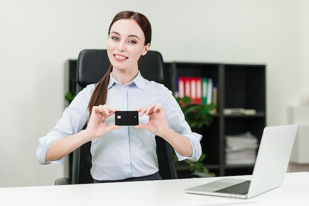 Geschäftsfrau, die online-zahlungen leistet und geld von der kreditkarte unter verwendung des laptops im büro verdrahtet