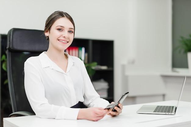 Geschäftsfrau, die online-zahlungen leistet und geld von der kreditkarte unter verwendung des smartphone verdrahtet