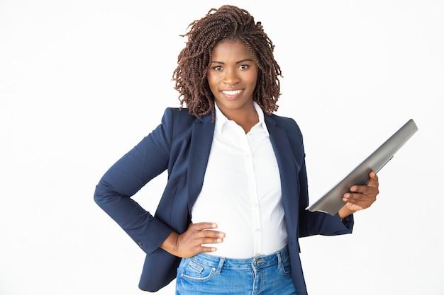 Geschäftsfrau, die ordner hält und an der kamera lächelt