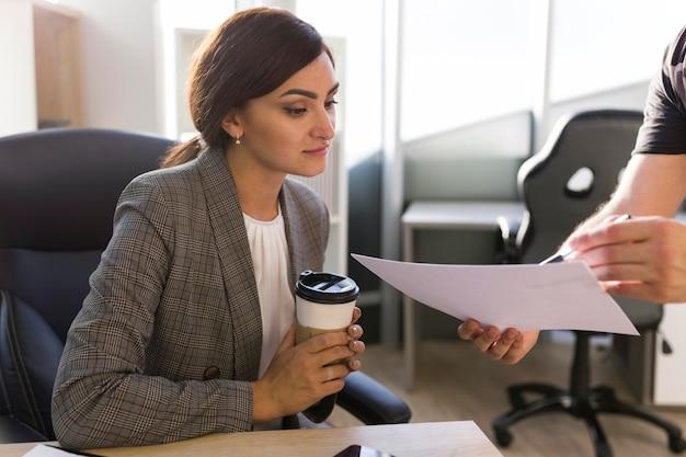Geschäftsfrau, die papiere im büro betrachtet