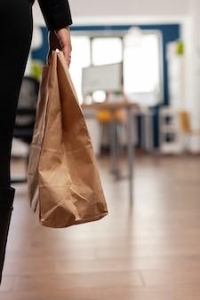 Geschäftsfrau, die papiertüte mit essensbestellung zum mitnehmen hält, die während der mittagspause im firmenbüro auf den schreibtisch legt