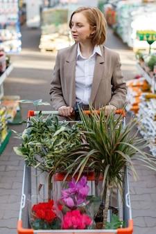 Geschäftsfrau, die pflanzen für ihr haus auswählt und kauft
