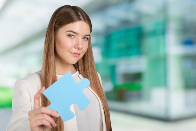 Geschäftsfrau, die puzzlespielstück hält