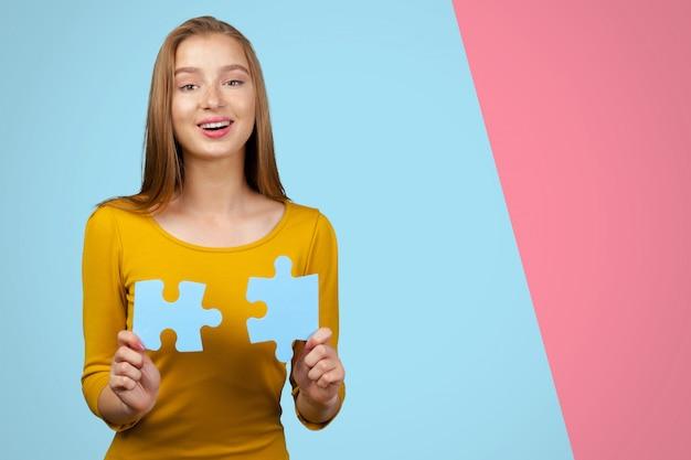 Geschäftsfrau, die puzzleteile hält. verbindungsgeschäftskonzept