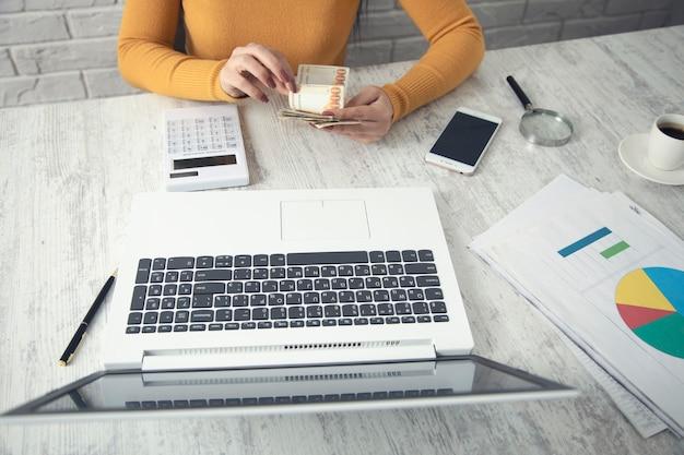 Geschäftsfrau, die rechner benutzt und geld hält